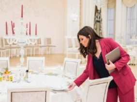 An Event planner specialist checkig the final retuches for formal wedding reception.